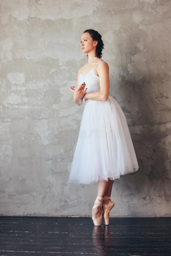 Ballet dancer ballerina in beautiful light blue dress tutu skirt posing in loft studio stock images