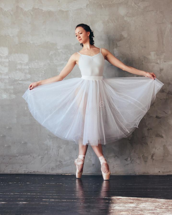 Ballet dancer ballerina in beautiful light blue dress tutu skirt posing in loft studio. The Ballet dancer ballerina in beautiful light blue dress tutu skirt royalty free stock images