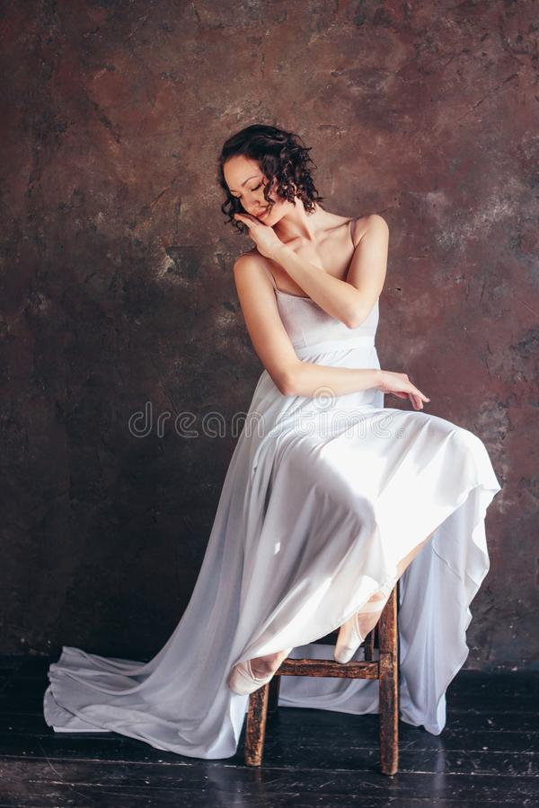 Ballet dancer ballerina in beautiful thin flying white dress is posing in dark loft studio stock photography