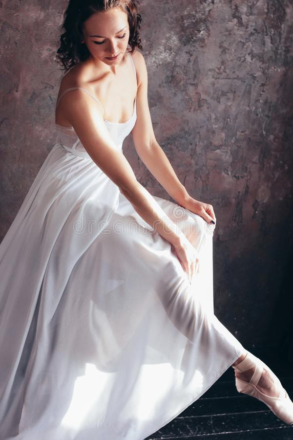 Ballet dancer ballerina in beautiful thin flying white dress is posing in dark loft studio. The Ballet dancer ballerina in beautiful thin flying white dress is royalty free stock photo