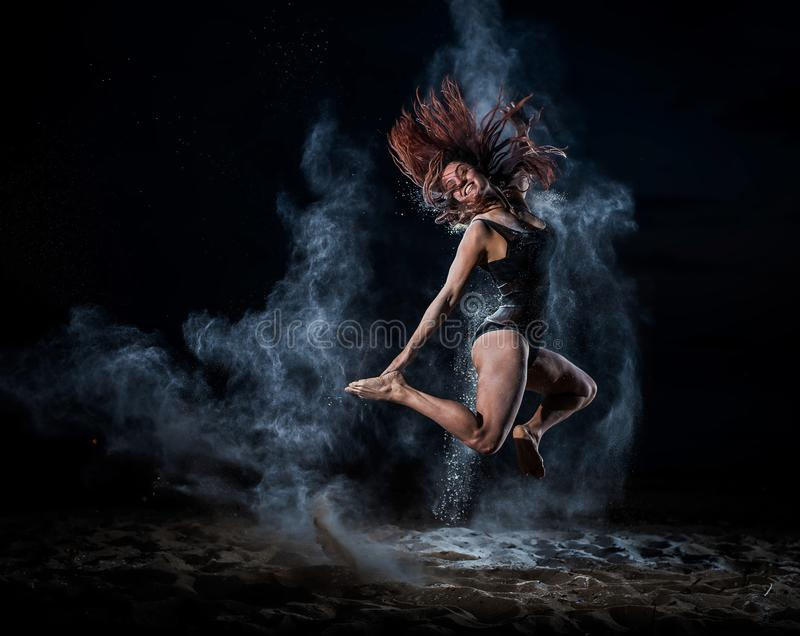 Ballet dancer in black bodysuit jumps high and dance with flour on the beach in the evening. Women`s street ballet. Flour, talc, royalty free stock photography