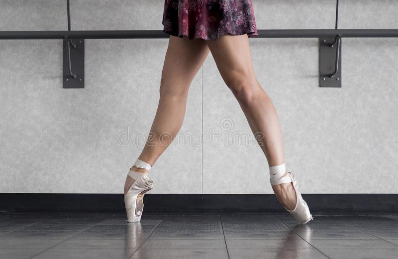 Ballet dancer en pointe in pointe shoes with bare legs in a wrap skirt during ballet class royalty free stock photo