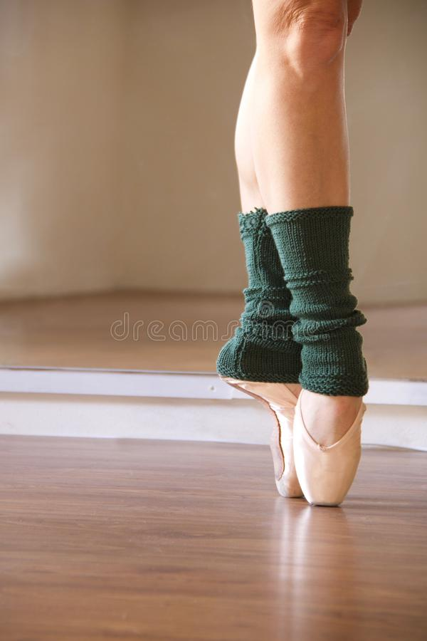 Ballet dancer feet on pointe shoes in fifth position. Ballet dancer feet on pointe shoes with green legwarmers in front of a mirror stock photography