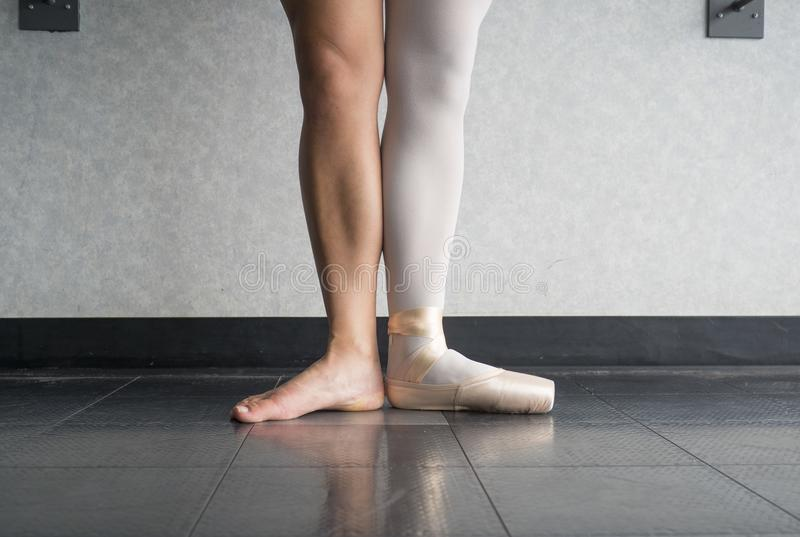 Ballet dancer in first position with one foot in a pointe shoe, and one bare leg royalty free stock photos