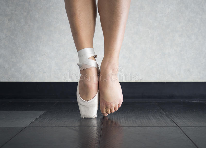 The ballet dancer`s balance on their pointe shoes, and the feet behind them stock images