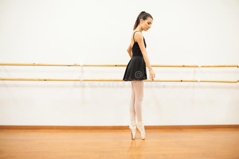 Ballet dancer tip toeing next to a barre. Full length portrait of a beautiful Hispanic young ballet dancer tip toeing next to a barre in a dance studio stock photos