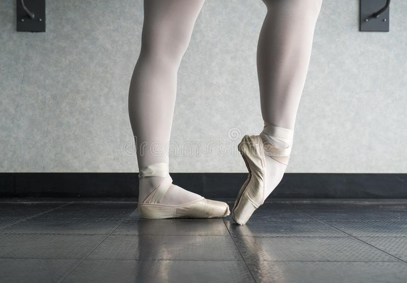 Ballet dancer warming up her feet in her pointe shoes for ballet class. Close up of a ballet dancer warming up her feet in her pointe shoes for ballet class royalty free stock photo
