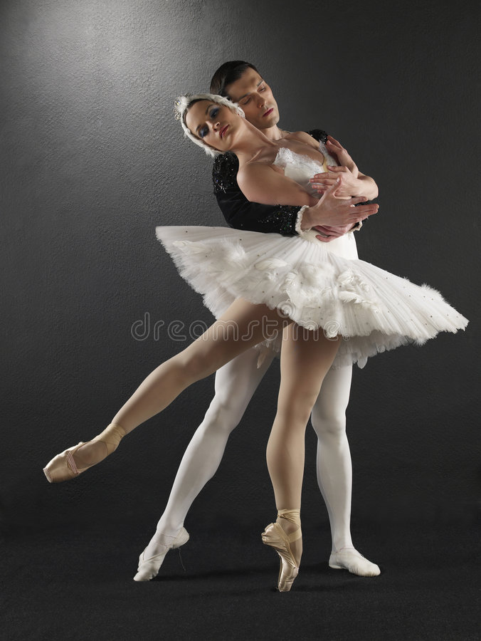 Ballet dancers. Two ballet dancers posing on a black background in ballet costumes