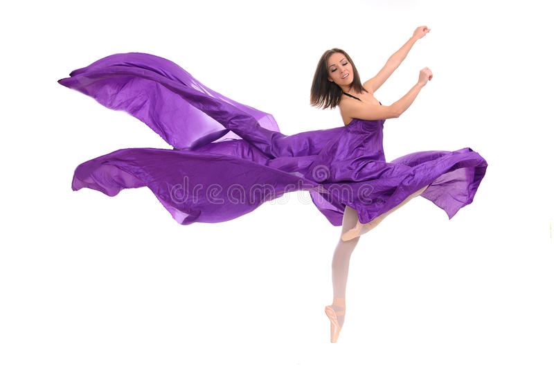 Ballet female dancer in violet gown. Professional ballet female dancer tiptoe in violet gown royalty free stock photography
