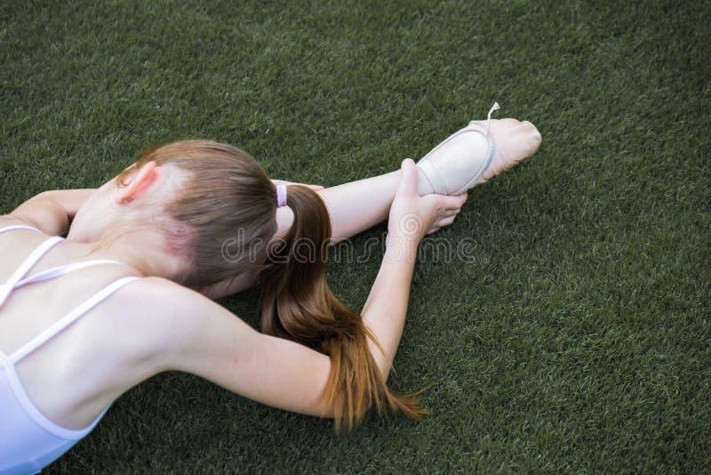 Ballet que estira en la hierba imagen de archivo