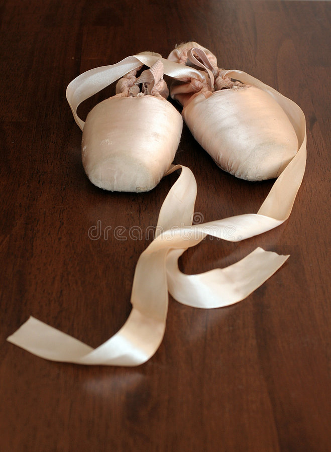 Ballet shoes. Pink ballet shoes on a dark wooden floor royalty free stock photography