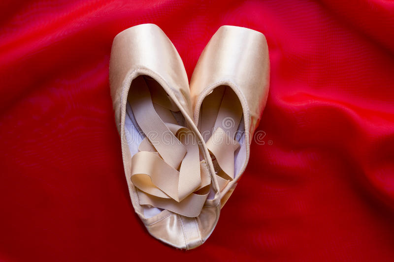 Ballet shoes. On delicate red silk background stock image