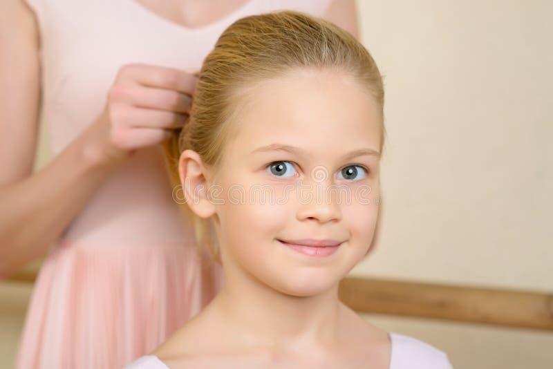 Ballet teacher fixing girls hairdo royalty free stock photos