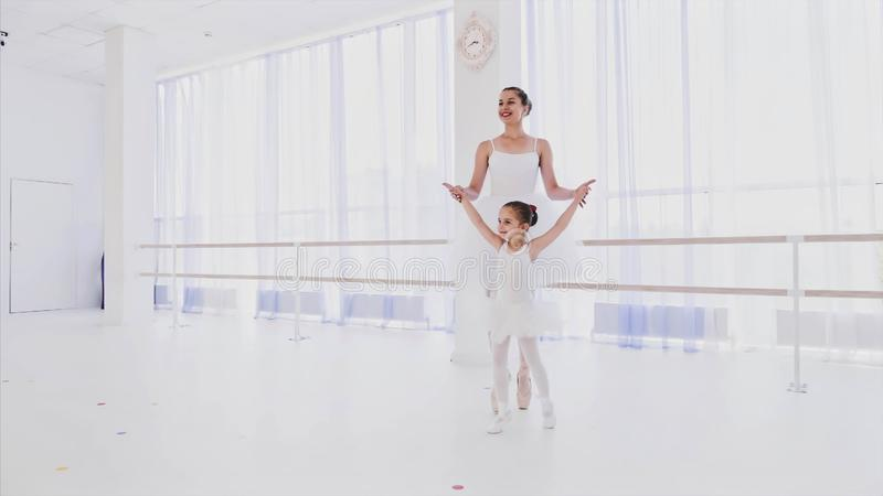 Ballet teacher with little girl training steps on tiptoe in pointes hold hands. royalty free stock photography