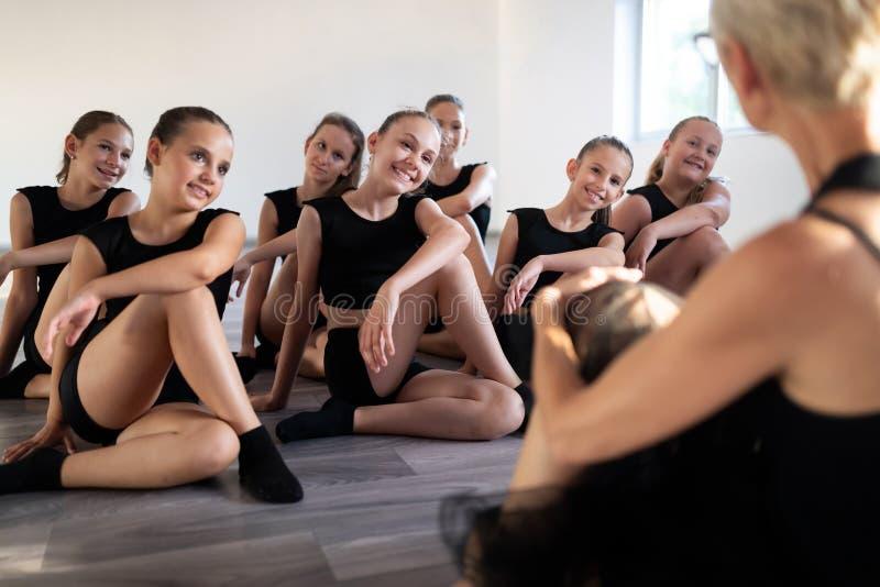 Ballet teacher and students ballerinas exercising in dance class in school stock photo