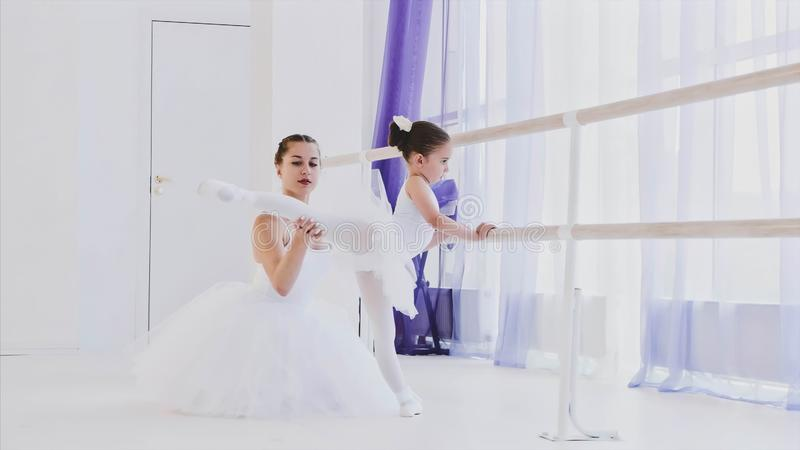 Ballet teacher is teaching little girl to stretch legs near the barre stand. stock photo
