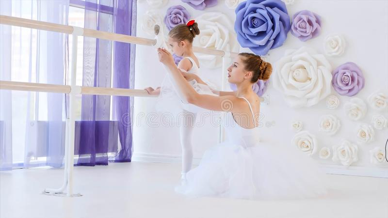 Ballet teacher is teaching little girl to stretch legs near the barre stand. stock image