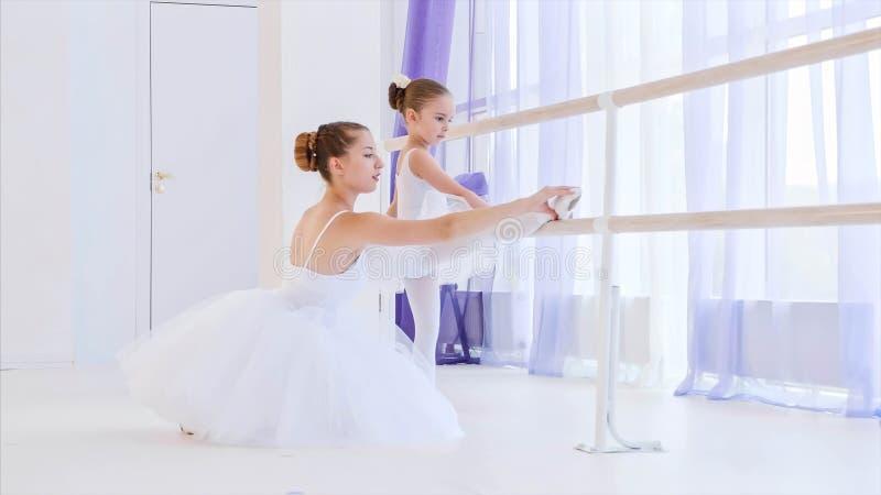 Ballet teacher is teaching little girl to stretch legs near the barre stand. stock photos
