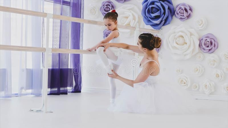 Ballet teacher is teaching little girl to stretch legs near the barre stand. royalty free stock images