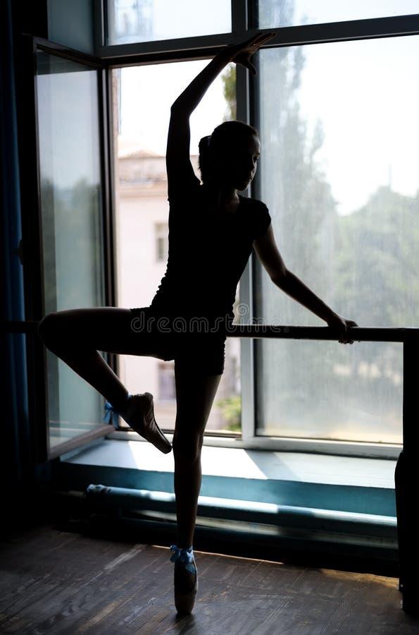 Balletdanser die bij de staaf door uitoefenen royalty-vrije stock afbeeldingen