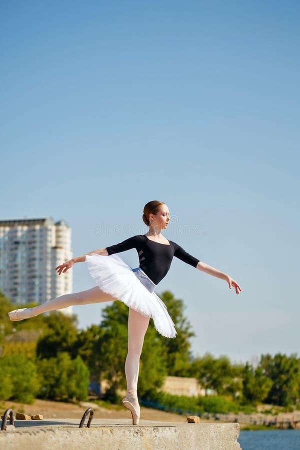 Balletdanser in tutu die op de promenade dansen arabesque royalty-vrije stock afbeeldingen