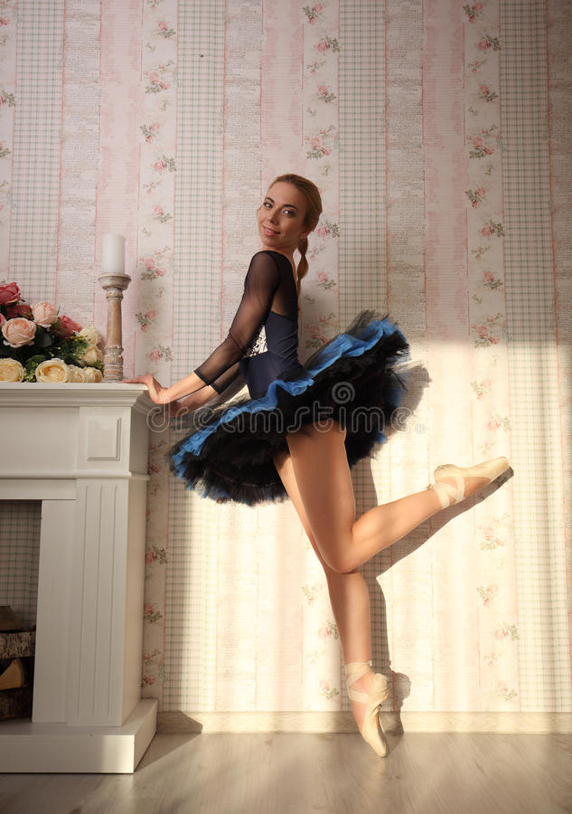Balletdanser in zonlicht in huisbinnenland, die zich op één been bevinden stock foto