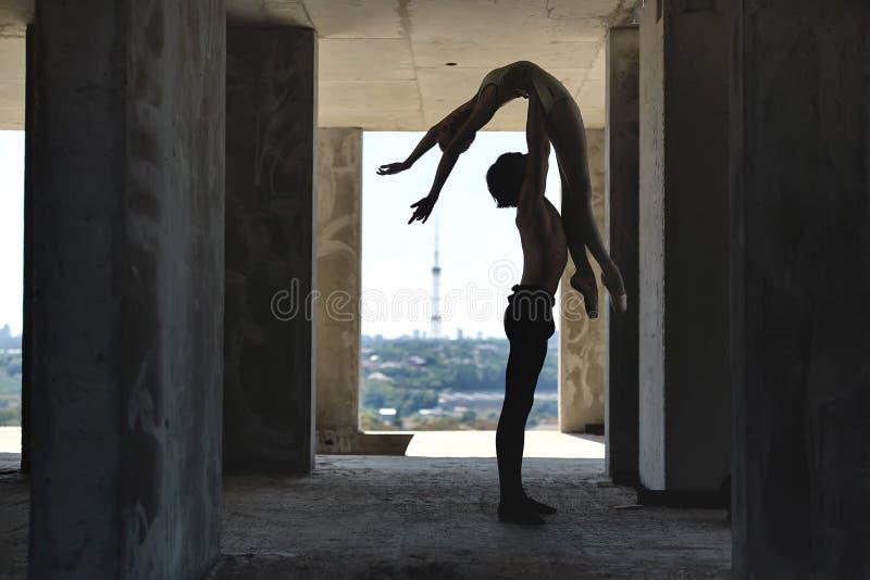 Balletdansers die bij de onvolledige bouw stellen stock foto