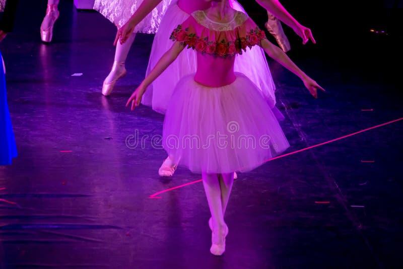 Balletdansers die onder Purper Licht met Klassieke Kleding een ballet op Onduidelijk beeldachtergrond uitvoeren stock afbeelding