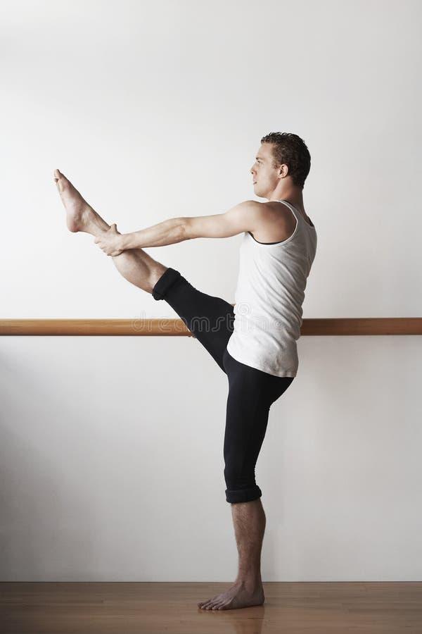 Ballett-Tänzer Practicing At Bar lizenzfreie stockfotos