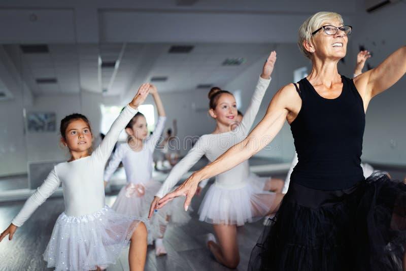 Ballettlehrer und Studentenballerinen, die in der Tanzklasse in der Schule trainieren lizenzfreie stockfotos