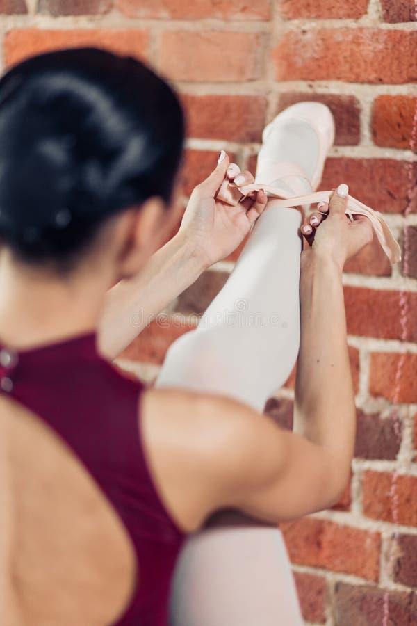 Balletttänzer, der das Band auf ihrem Bein einwickelt lizenzfreie stockbilder