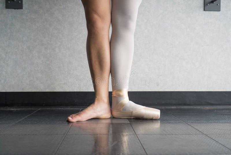 Balletttänzer in erster Stelle mit einem Fuß in einem pointe Schuh und ein bloßes Bein lizenzfreie stockfotos