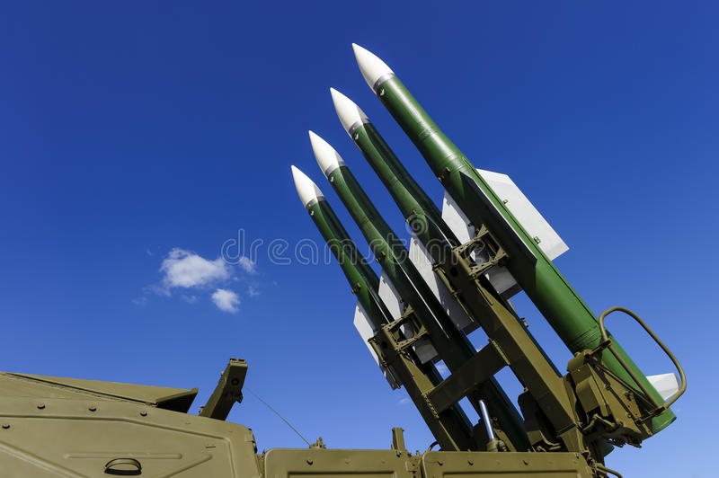 Ballistic rocket launcher. With four cruise missiles on powerful mobile transportation with blue sky and white clouds on background, antiaircraft forces stock photo