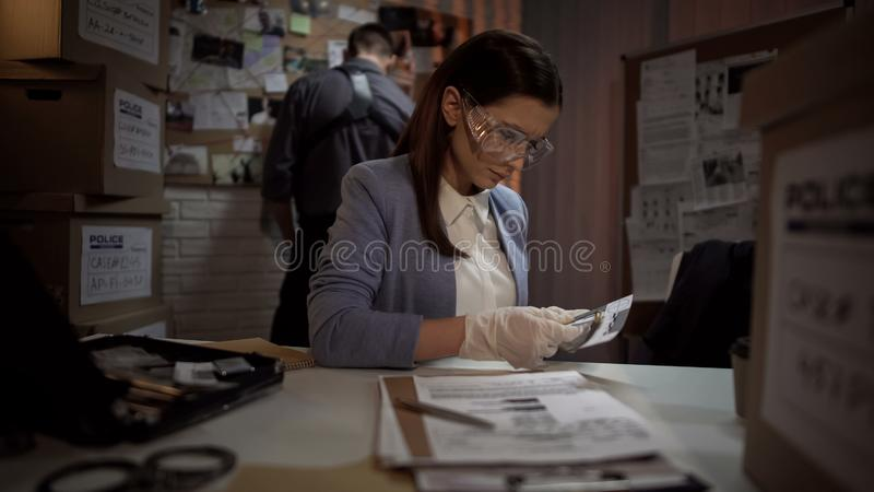 Ballistics professional determining information about bullet, police office stock photo