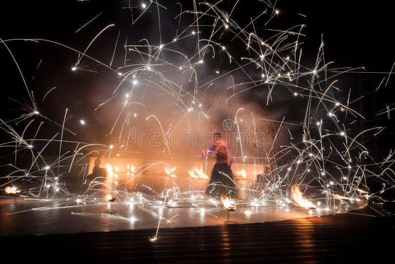 Ballo di stupore di manifestazione del fuoco Ballerini del fuoco in bei costumi che giocano con le fiamme variopinte immagine stock libera da diritti
