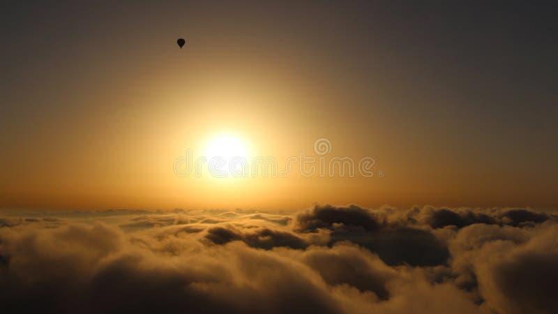 Ballon à air chaud au-dessus des nuages dans le lever de soleil image stock