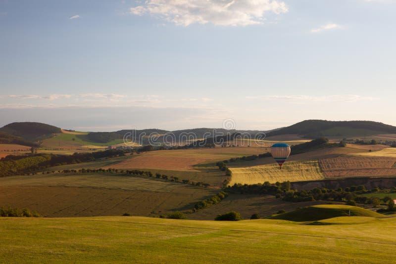 Ballon à air chaud volant au-dessus d'un terrain de golf et d'une vallée au coucher du soleil photos libres de droits