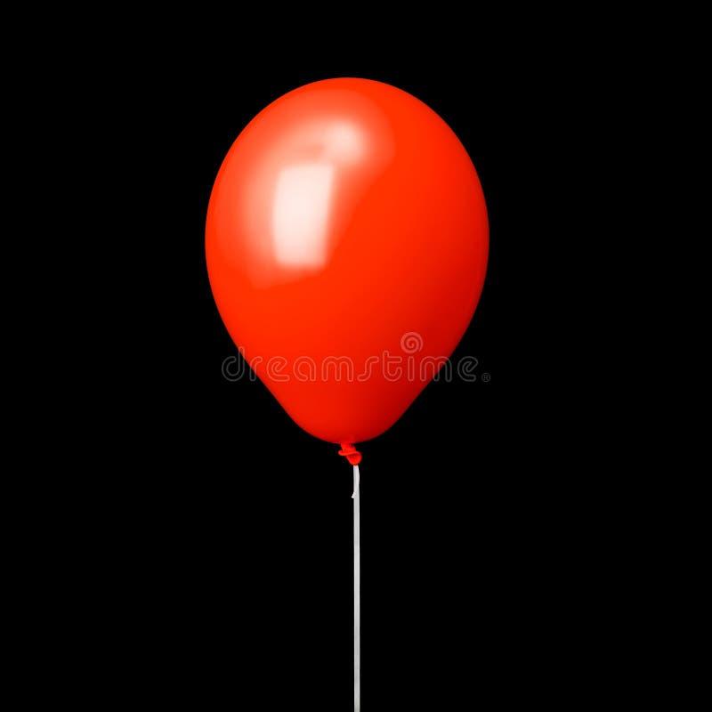 Ballon à air rouge sur le ruban blanc d'isolement sur le noir images stock