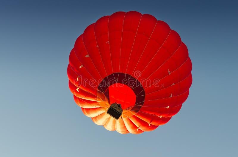 Ballon ? air d'un rouge ardent contre le ciel bleu photo stock