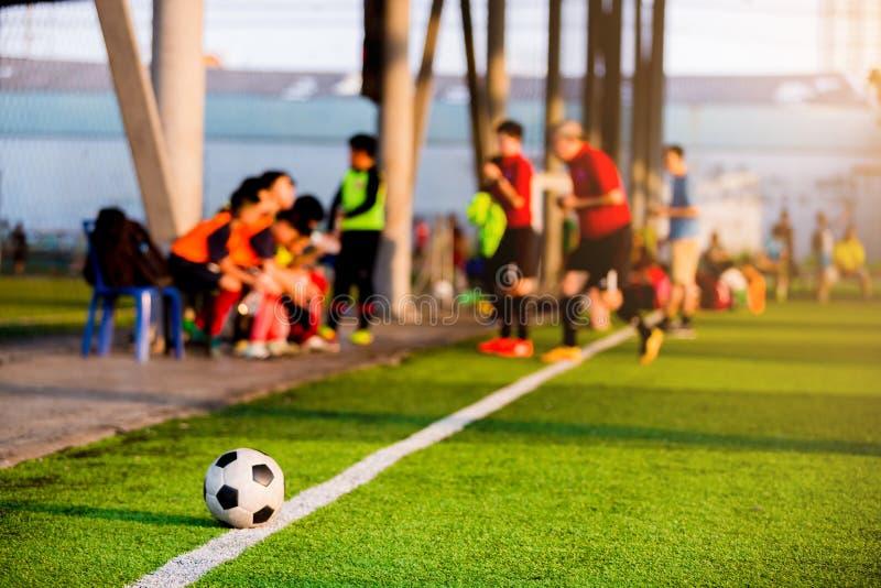 Ballon de football aux lignes de touche sur le gazon artificiel avec trouble des footballeurs image libre de droits