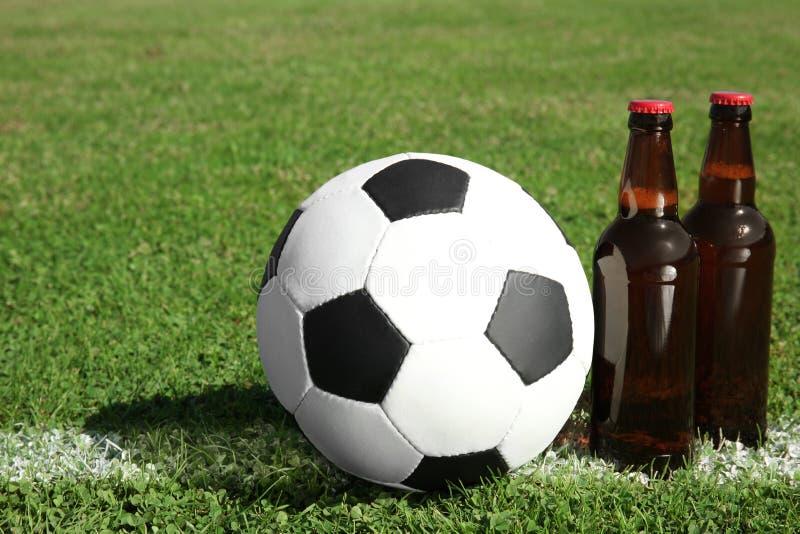Ballon de football avec la boisson sur des gras verts de terrain de football photographie stock