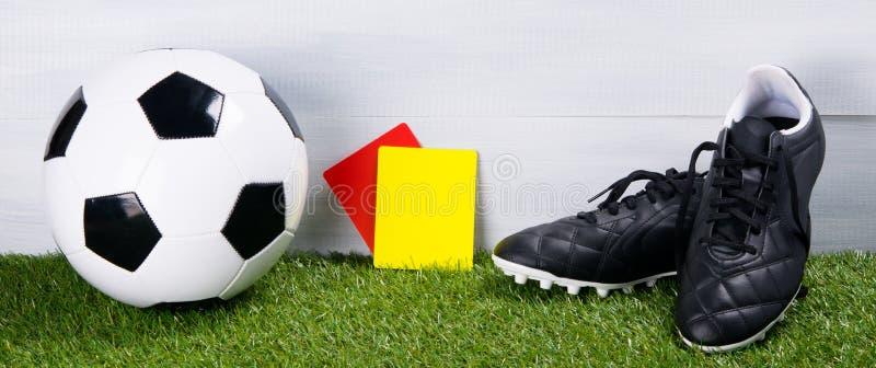 Ballon de football, bottes, cartes de pénalité pour l'arbitre, mensonge sur l'herbe, sur un fond gris images libres de droits