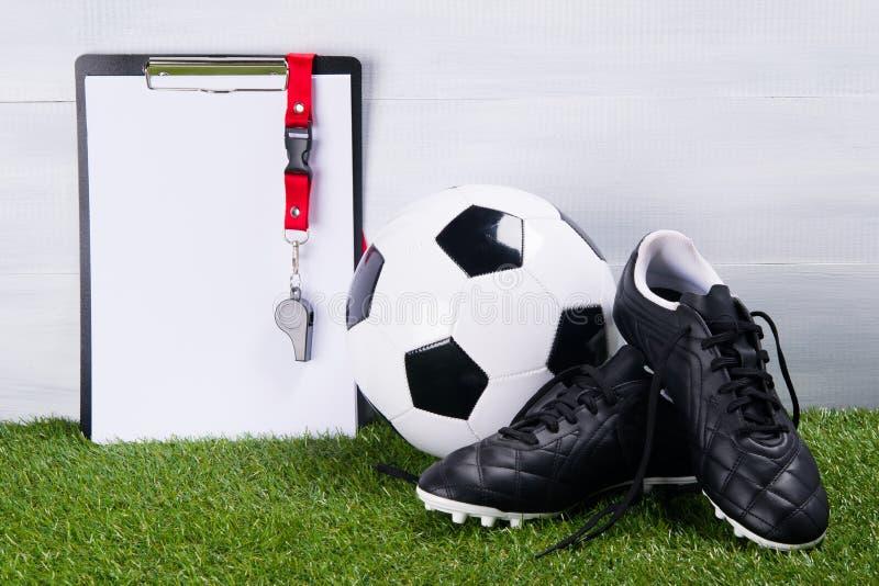 Ballon de football, bottes et sifflement sur un comprimé pour écrire, pour un juge, le mensonge sur l'herbe, sur un fond gris image stock