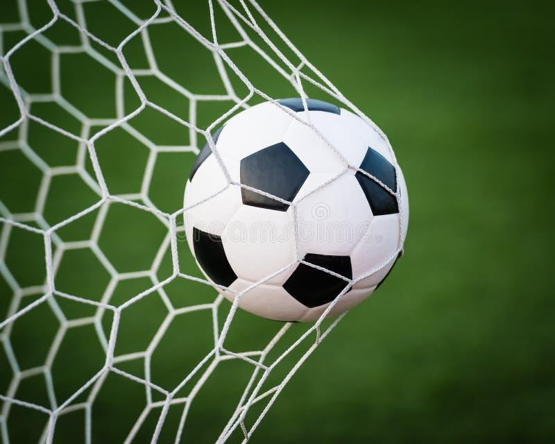 Ballon de football dans le réseau de but photographie stock
