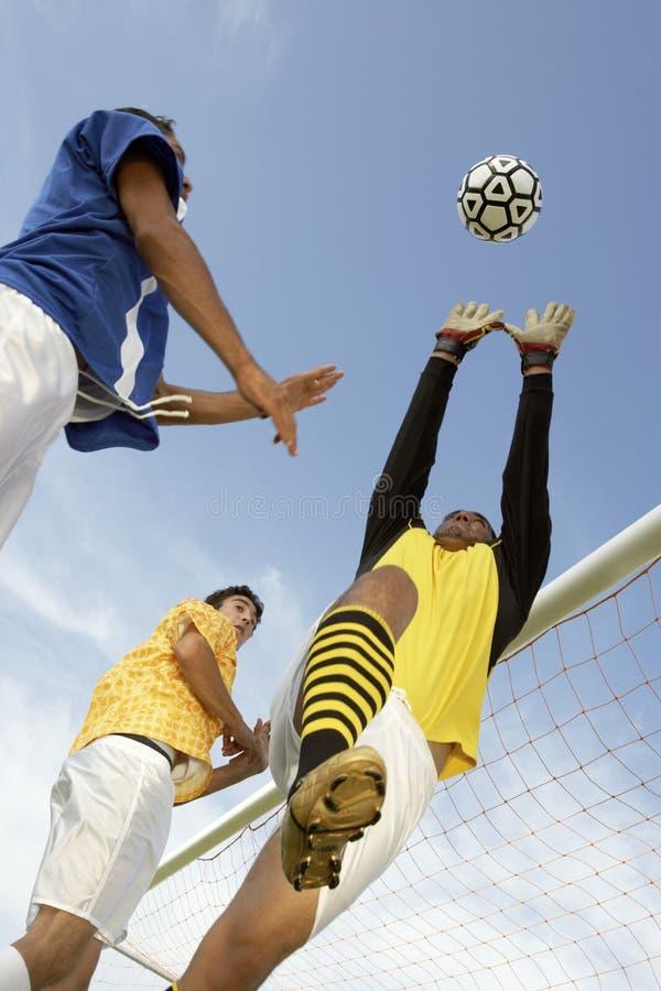 Ballon de football de titre de joueur tandis que gardien de but essayant de le sauver photographie stock libre de droits
