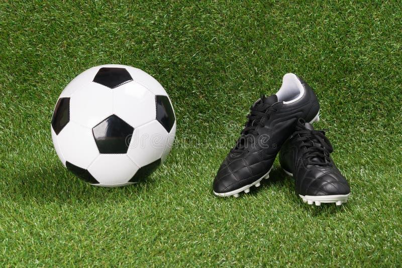 Ballon de football et bottes sur un gazon artificiel vert photos libres de droits