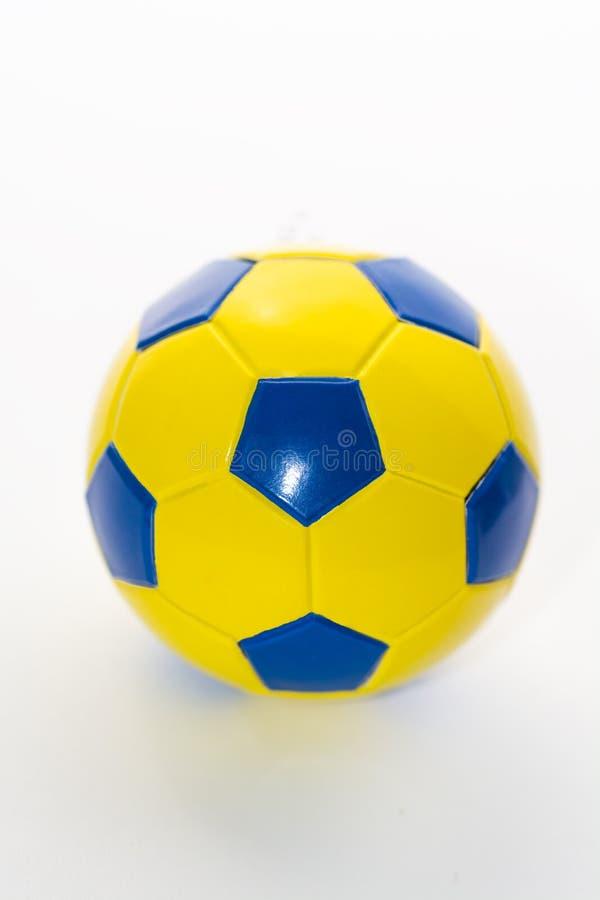 Ballon de football jaune-bleu sur un fond blanc, image libre de droits