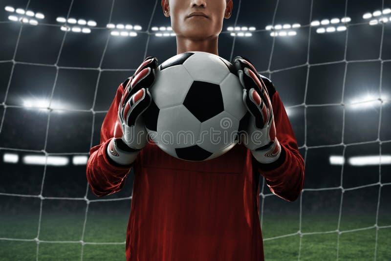 Ballon de football de prise de footballeur photographie stock
