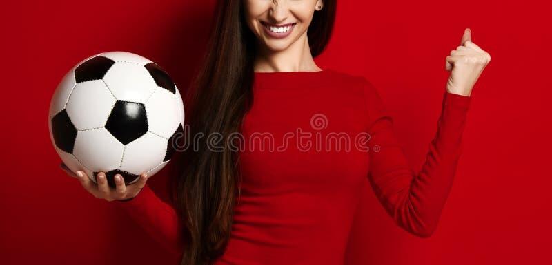 Ballon de football de prise de joueuse de femme de sport de fan célébrant le signe oui de gain de succès d'exposition heureux ave photographie stock libre de droits