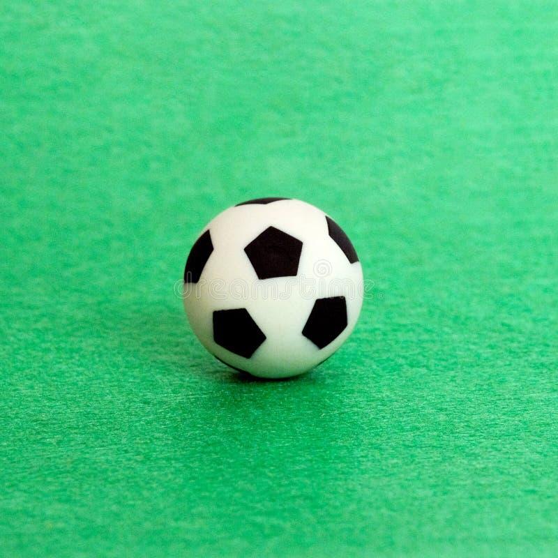Ballon de football de souvenir sur un fond vert de feutre Profondeur de zone Une photo carrée photographie stock